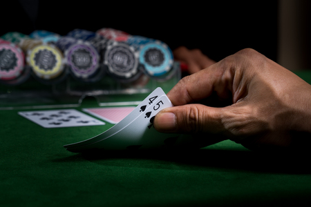 A hand holding the cards show face values nine to win a blackjack game on green table and blurry stacked chips background in the casino Stockfoto