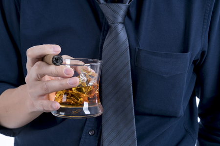 selective focus at a glass of whiskey with ice and cigar in the businessman hand wear blue shirt and the tie was unravel in relaxtion after working time