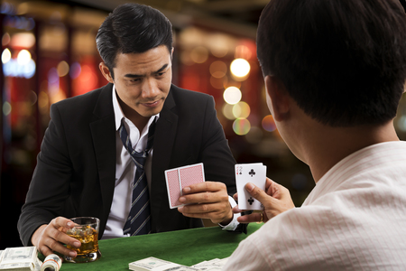 The young man looking up from high stakes poker game in casino club