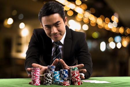 Porträt benutzte der junge Spielermann die Hände, die großen Stapel der farbigen Spielertabelle der farbigen Schürhakenchips für das Wetten auf Kasinoclubhintergrund drücken