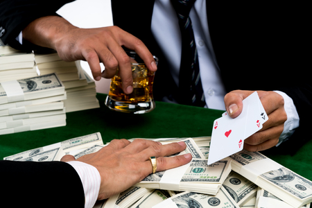 The winner gambler holding whiskey glass and show triple aces in his hand, the stack of banknote on green casino table, white background with business casino concept  Stock Photo