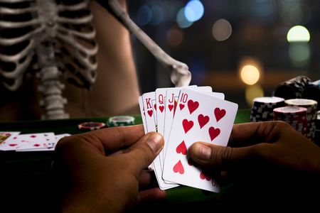 The gambler play poker game with a human skeleton and show winner with Hearts Suit Straight Flush is over the opponent and collect bets on the green table, casino club background  Stock Photo