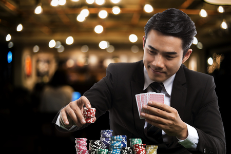 portrait of the young asian gambler is putting bets into the piles of chips, in the left hand holding poker card, on casino background, business casino concept Reklamní fotografie