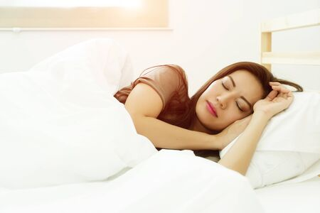 The beautiful lady lying on the right under white blanket on mattress with comfortable sleeping in the bedroom, with orange light rays background