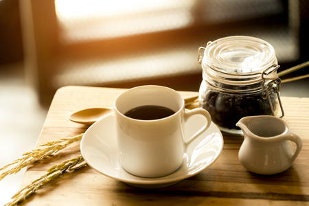 Hot coffee in white cup and seed in glass jar, with wooden spoon on plank table, concept coffee time Stock Photo