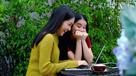 when: The two asian lovely girls were excited and cheerful when to get a good news on internet from laptop computer, Dolly shot with teenager lifestyle concept Stock Photo