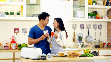 tea hot drink: Young asian couple happy with drinking the coffee and chatting in the kitchen