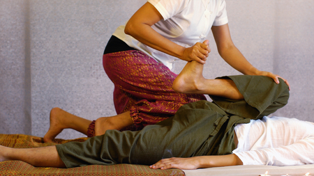 De therapeut die werkt en handelt op de lichaamsdruk, gebruikte de knie op het been van de man op de grond, het Thaise massageconcept. Stockfoto
