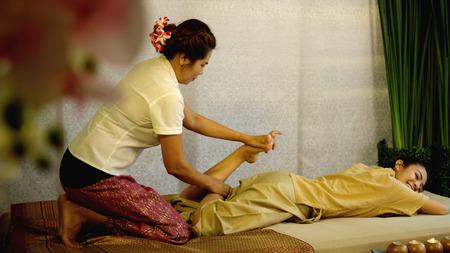 다리 마사지를하고있는 태국 마사지 팀, 예쁜 고객이 바닥에 누워서 다리를 접은 채로 길게 누르십시오. 좌우 스왑 태국 마사지 개념