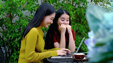 The two asian lovely girls were excited and cheerful when to get a good news on internet from laptop computer, Dolly shot with teenager lifestyle concept Stock Photo