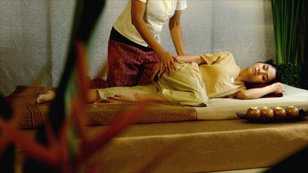 de masseuse massage heup van mooi meisje liggend op matras, traditionele Thaise therapie, Thaise massage concept Stockfoto