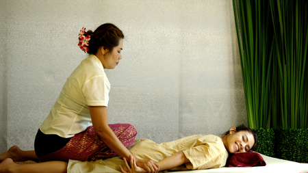 The masseuse pulls the arms and bending back of client, traditional therapy for spine for pretty woman, Thai massage concept