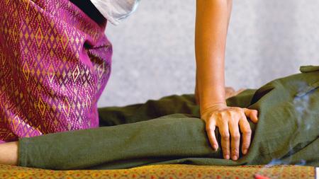 Il massaggio thailandese prevede lo stretching e il massaggio profondo, il lavoro del massaggiatore e l'azione sul corpo con la pressione con il cliente l'uomo indossa vestiti comodi, il concetto di massaggio thailandese Archivio Fotografico - 85052819