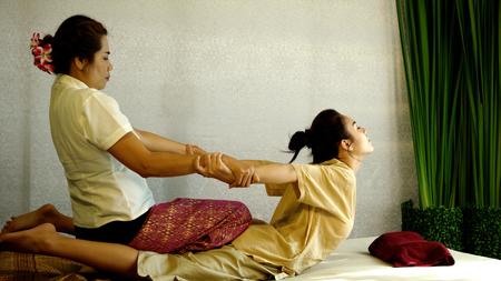 안마사는 팔을 끌어 당기고 클라이언트의 굽힘, 예쁜 여자를위한 등뼈에 대한 전통적인 치료법, 태국 마사지 개념