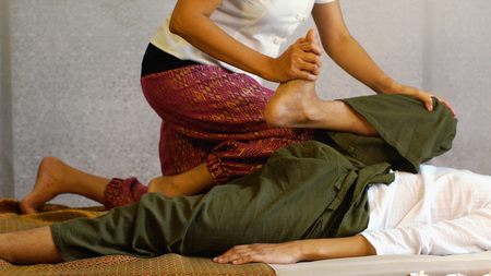 The therapist working and acting on the body pressure used knee on mans leg lying on floor, Thai massage concept. 免版税图像