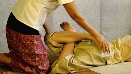 back ache: Thai masseuse bending the leg massage, pretty client woman lying on the floor and then fold the leg comes up, press and hold. Swap the left and right, Thai massage concept