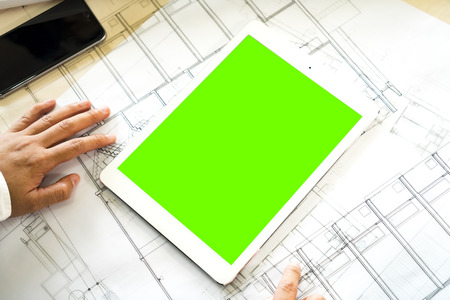 Close up and mock up green screen display on white tablet in businessman, smartphone and construction plan on wooden table.
