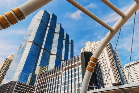 The ant eyes view of Beautiful bridge of skywalk at the center connected to electric train station, Bangkok at business city of Thailand with blue sky