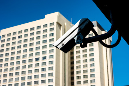 Surveillance Security Camera or CCTV in for protection system under the bridge has shadow and blur background with building and blue sky Stock Photo