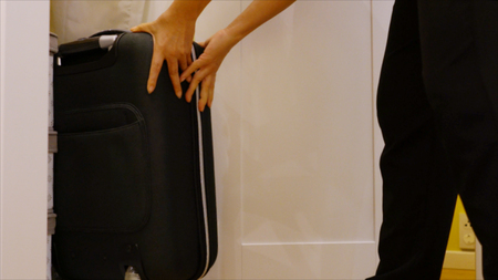 hands woman keeping a black suitcase into the white wardrobe Stock Photo