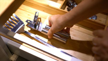 kitchen cabinets: Close up the hand of female opened the spoon drawer to pick up a can opener out and close them