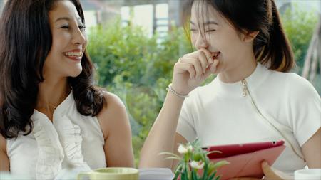 bella madre e adorabile figlia adolescente si divertono con i tablet e ridono, condividono un momento di relax insieme