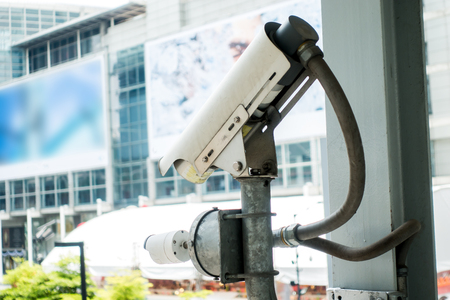 Surveillance Security Camera or CCTV in for protection system under the bridge and blur background with building, copy space