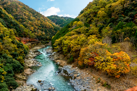 The beautiful landscape landmark of the Katsura river and with the Togetsukyo Bridge in the distance, in Arashiyama area in autumn at Kyoto, Japan