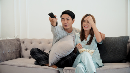 Young man and pretty woman sitting on the couch in the living room, they are enjoy to watch television. husband use remote control to change the channel and eating popcorn Stockfoto