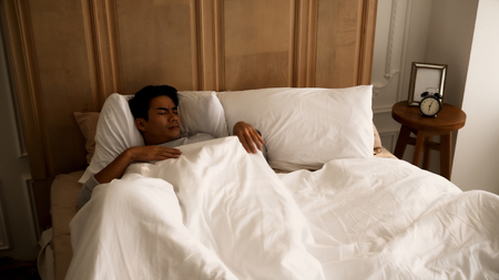 The young man sleeping under white blanket on the bed at six o'clock in morning
