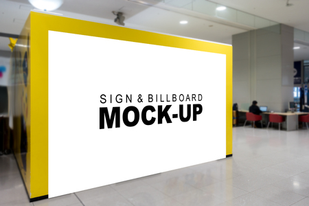 Mock up blank billboard on yellow panel of booth sales at airport terminal , Empty space for advertising or promotion information, blurred background with seat and surf the Internet