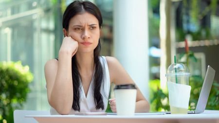 Close up the young woman sitting and hold the head on hand with feeling stressed and serious Stock Photo