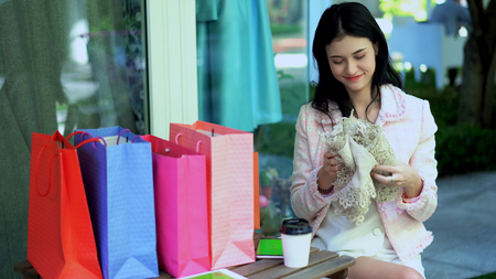 Selective focus at the pretty woman feeling admired a beautiful lace and many shopping bag on desk