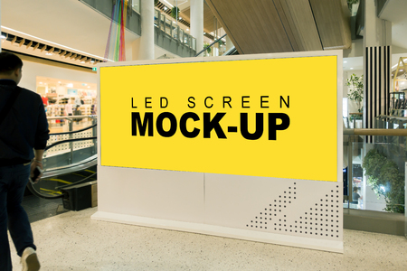 Side view the mock up large blank yellow screen billboard near escalator with clipping path at front of escalator in mall, blurred young man is looking, empty space for advertising or information Banco de Imagens