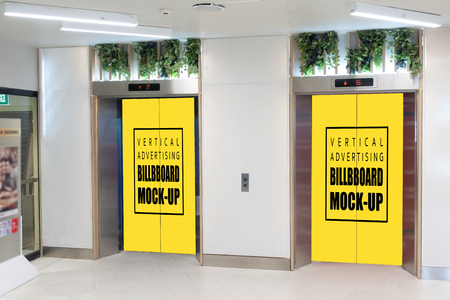 Two mock up vertical blank yellow billboard indoors advertising on doors of elevator cabin with clipping path Banco de Imagens
