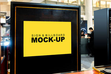 Mock up blank billboard or signboard on black backdrop with clipping path, yellow empty space or advertising or information for promotion at front of shop in mall Banco de Imagens