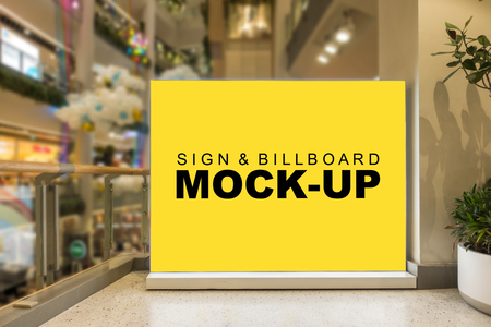 Mock up blank large yellow screen billboard or signboard stand with clipping path in shopping mall, empty space for message or media advertisement indoors.