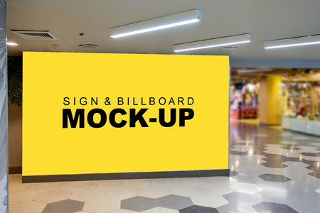 Mock up large blank yellow screen billboard with clipping path placed on the in mall and blurred shop in background, empty space for advertising or information, advertising concept