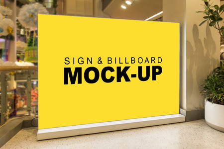 Mock up blank large yellow screen billboard or signboard stand with clipping path in shopping mall, empty space for message or media advertisement indoors. The view on the left