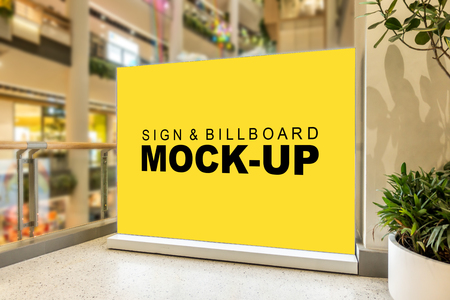 Mock up blank large yellow screen billboard or signboard stand with clipping path in shopping mall, empty space for message or media advertisement indoors with the view on the right