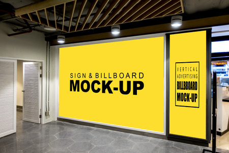 Mock up large blank yellow screen billboard and vertical signboard near doors with clipping path at front of superstores and blurred shelf in background, empty space for advertising or information