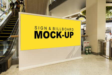 Mock up large blank yellow screen billboard on modern frame near escalator with clipping path at side of escalator in mall, blurred young man is looking, empty space for advertising or information