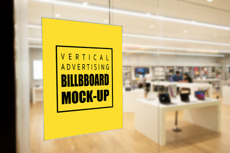 Mock up blank vertical yellow screen billboard or signboard with clipping path on the glass panel of modern store in the shopping mall, empty space for message or media advertisement indoors.