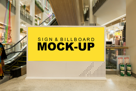 Mock up large blank yellow screen billboard on modern frame near escalator with clipping path at front of escalator in mall, blurred young man is looking, empty space for advertising or information Banco de Imagens