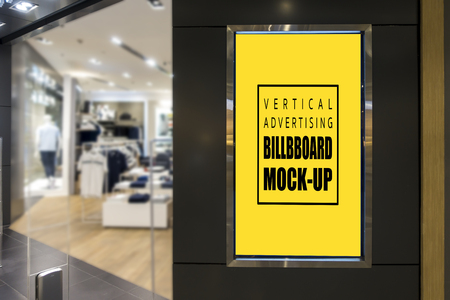 Mock up vertical advertising blank yellow screen billboard with clipping path for insert text message or media content at front of fashion clothing store, marketing and advertisement concept Banco de Imagens
