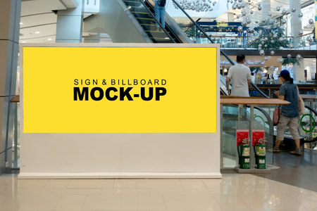Mock up large blank horizontal billboard for advertising with clipping path, Empty space for promotion or information signboard stand near escalator in shopping mall, blurred people walking up.