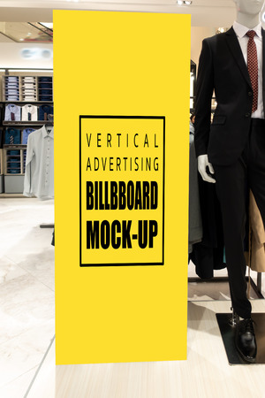 Mock up vertical blank billboard with clipping path to show promotion or discount in mens suit and clothing shop, tall yellow screen empty space for insert text or advertising in shopping mall Banco de Imagens