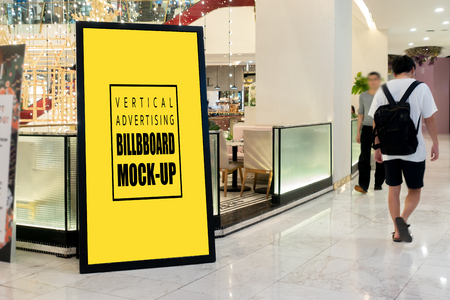 Mock up perspective the vertical blank billboard in black frame at walkway of shopping mall  , Yellow screen empty space for insert text or advertising Banco de Imagens