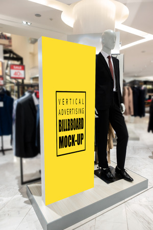 MMock up perspective vertical blank billboard   to show promotion or discount in suit and clothing shop, yellow screen empty space for insert text or advertising in shopping mall
