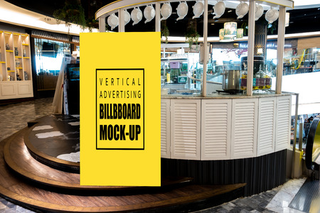 Mock up vertical blank billboard standing at front of tea booth in shopping mall, Yellow screen empty space for insert text or advertising
